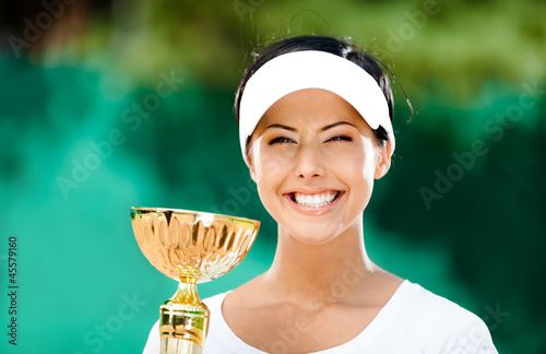 Tennis player won the cup at the sport contest. Trophy