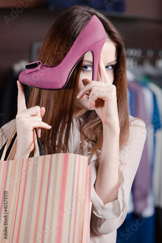 Woman plays with excellent fuchsia shoes at the store