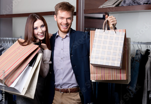 Cheerful couple show their purchases after shopping
