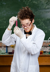 Mad professor stares at the beaker with red water