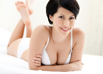 Woman in underwear is lying in the bed with white bed linen