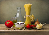 Pasta and vegetables on wooden tabletop against grunge wall. poster