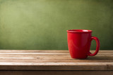 Red mug on wooden tabletop against grunge green wall poster