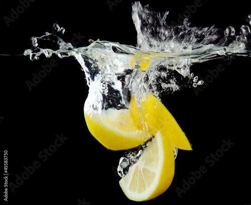 Foto op Canvas Opspattend water Sliced lemon in the water on black background