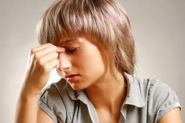 A woman having a headache, closeup