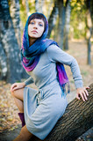 The girl in a scarf and in a knitted dress sits on a tree.