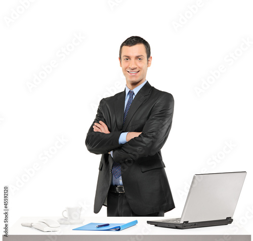A confident businessman posing at his workplace