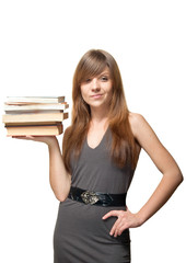Pretty young woman smiles and holds a stack of books