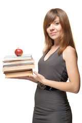 Pretty young woman  with the apple and a stack of books gently s