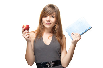 Pretty young woman with the apple and a book sweetly smiles