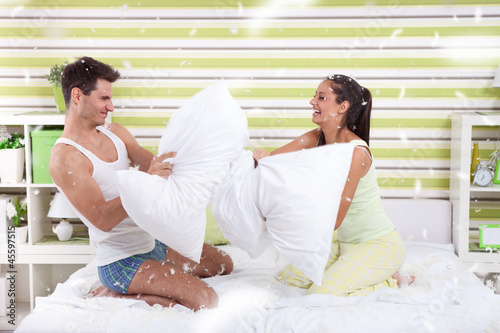 Young couple having fun with pillows at home