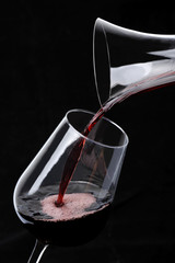 Red Wine pouring into glass from decanter