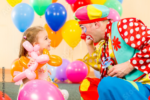 happy child girl and clown playing on birthday party