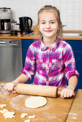 Little girl kneading dough with rolling pin on table