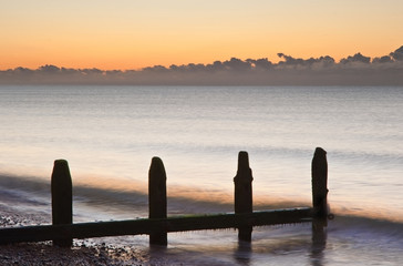 Old groynes on beach last defense at sunrise against tide