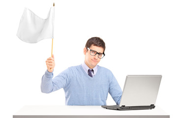 Sad man sitting with laptop and holding a white flag gesturing d