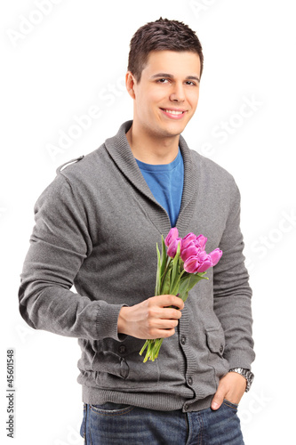 Smiling handsome male holding tulips