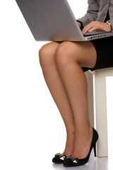 Hands and legs of a business woman working on a laptop