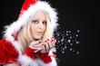 Junge hübsche blonde Santa Frau pustet Sternen Staub