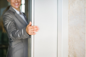 Closeup on business woman hand holding elevator door