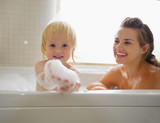 Baby playing with foam while taking bath with mother