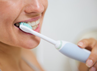 Closeup on woman brushing teeth with electric toothbrush