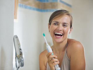 Happy young woman after brushing teeth with electric toothbrush