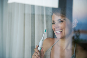 Young woman with electric toothbrush and looking in window