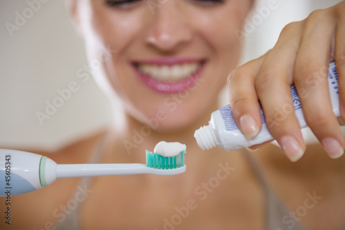 Closeup on hands squeezing toothpaste on electric toothbrush