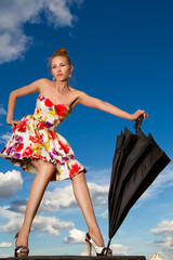 Flying girl with umbrella in the blue blue sky