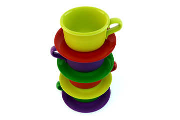 Colored stacked coffee cups and saucer on white background