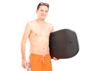 A male surfer posing with his surfboard