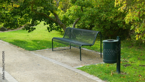 Leinwanddruck Bild grüne oase mit einer grünen parkbank aus metall