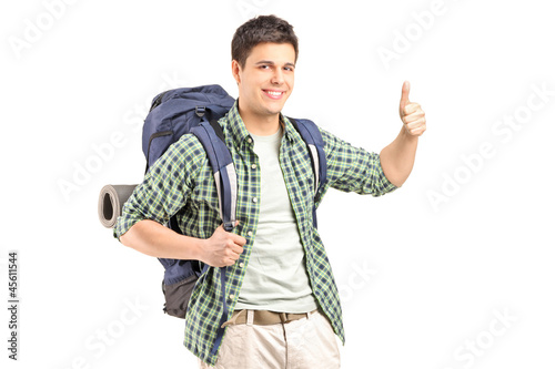 A male hiker with backpack giving a thumb up