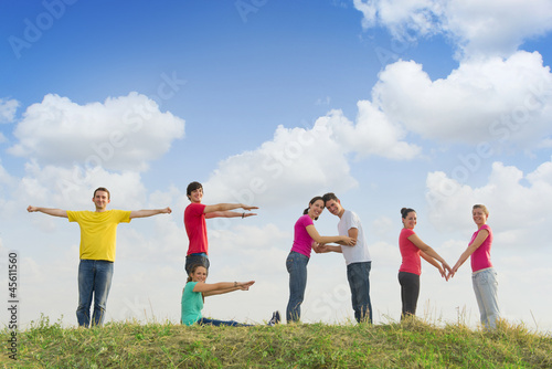 Group of people spelling word TEAM outdoors in nature