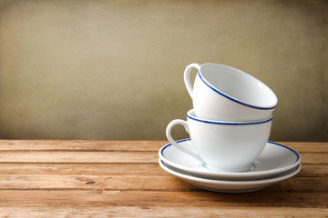 Two coffee cups on wooden tabletop against grunge background