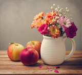 Beautiful flower bouquet and fresh apples on wooden tabletop poster