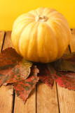 Pumpkin and autumn leaves on wooden tabletop poster