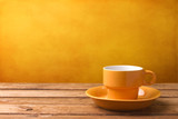 Yellow coffee cup on wooden tabletop poster
