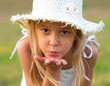 Cute little girl on the meadow blowing a kiss toward you