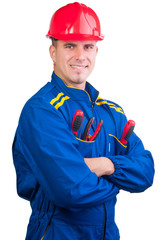 Young handsome mechanic with hard hat and tools and in overalls