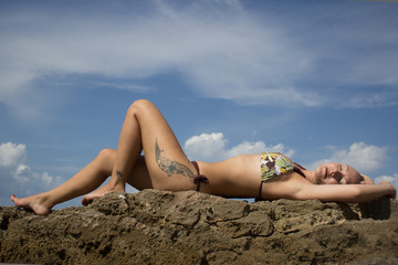 Brunette woman with a bikini, lie down at the beach