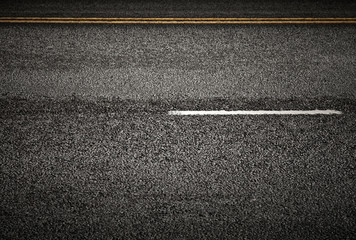 Road marking: white and yellow lines on the dark asphalt
