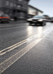 On the wet road with fast approaching cars