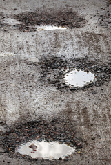 Damaged wet road with holes