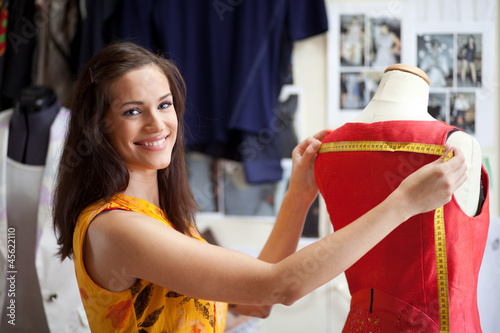Fashion designer measuring a dress. Shallow depth of field. - 45622110