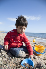 bambino che gioca in riva al mare  in inverno