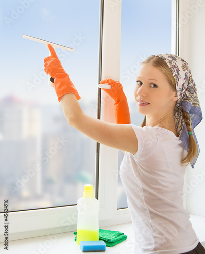 young housewife washing the window