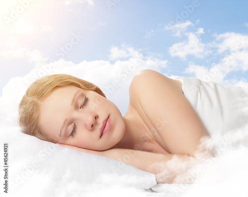 Leinwanddruck Bild beautiful young woman sleeping on a cloud in the sky