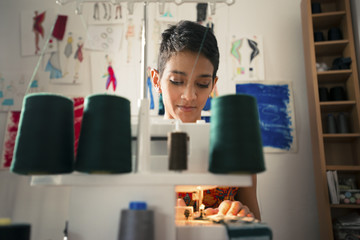 Young woman at work as tailor in fashion design atelier